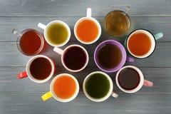 Copos do chá diferente na tabela de madeira, Imagem de Stock Royalty Free