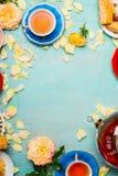 Copos do chá, do potenciômetro, dos bolos e das pétalas das flores na luz - fundo azul Imagem de Stock