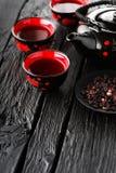 Copos do chá e do bule na tabela preta Imagens de Stock