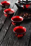 Copos do chá e do bule na tabela preta Imagens de Stock Royalty Free