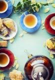 Copos do chá com as flores dos bolos e do potenciômetro e das rosas do chá no fundo chique gasto do azul de turquesa Foto de Stock Royalty Free