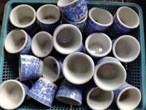 Copos do estilo chinês usados bebendo o chá colocado na cesta azul fotografia de stock