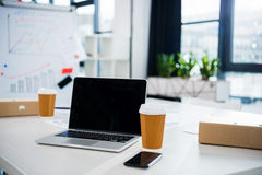 Copos do laptop, do smartphone e de café no local de trabalho no escritório vazio Fotos de Stock Royalty Free
