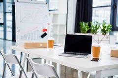 Copos do laptop, do smartphone e de café no local de trabalho no escritório vazio Foto de Stock Royalty Free