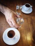 Copos e água de café na tabela de madeira Imagem de Stock Royalty Free