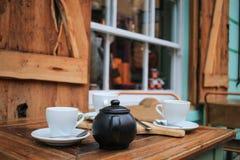 Copos e bule de chá em uma tabela em um café exterior Fotografia de Stock