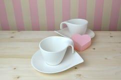Copos e pires da porcelana com símbolo do coração Imagens de Stock Royalty Free