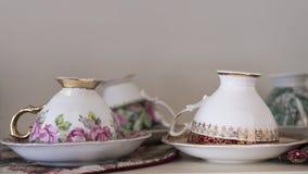 Copos e pires de chá ímpares da porcelana da porcelana de osso Foto de Stock