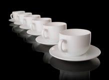 Copos e saucers brancos em um fundo preto Foto de Stock Royalty Free