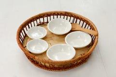 Copos pequenos da porcelana na cesta de bambu no fundo branco foto de stock