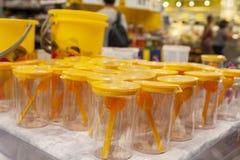 Copos plásticos com uma colher de medição na janela da loja imagem de stock