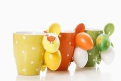 Copos pontilhados decorados com colheres e os ovos da páscoa plásticos Imagem de Stock Royalty Free
