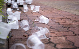 Copos vazios da água no assoalho na trilha de competência da maratona Imagens de Stock