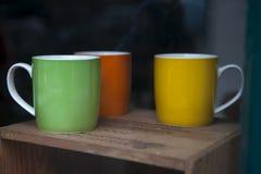 Copos verdes e amarelos vermelhos do esmalte na janela Foto de Stock Royalty Free