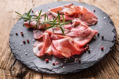 Coppa di Parma ham on slate board with rosemary salt and pepper.  royalty free stock photo