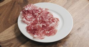 Coppa on white plate on wood table. Wide photo Royalty Free Stock Image
