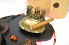 Copper ashtray with cigar and monkeys and amber earrings Royalty Free Stock Image