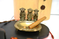 Copper ashtray with cigar and three monkeys Stock Photos