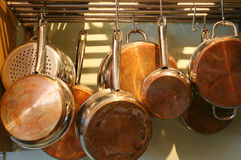 Copper Bottomed Pots and Pans. A selection of well-used copper-bottomed saucepans hanging from a rack Royalty Free Stock Images