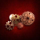 Copper and brass gear on the gold metallic wall. Stock Photos
