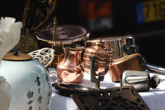 Copper and brass utensils on a French flea market. Close view of ancient copper and brass utensils. Paris flea market (France Stock Photography