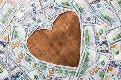 Copper heart shape in center of dollar money background. Copper bronze heart shape in center of dollar money background stock image