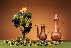 Copper carafe and fresh grapes Royalty Free Stock Images