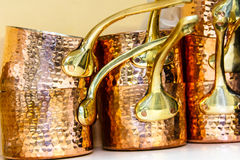 Copper casseroles are on the shelf. Stock Photography