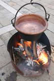 Copper cauldron full of water over the open fire. Big copper cauldron full of water over the open fire royalty free stock photography