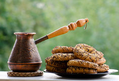 Copper Cezve of coffee in the open air, a plate of cookies Royalty Free Stock Images