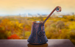 Copper Cezve with hot coffee on a windowsill, blurred autumn bac Royalty Free Stock Images