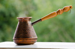 Copper Cezve with hot coffee on a windowsill Royalty Free Stock Images