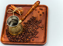 Copper coffee pot with coffee beans and cinnamon sticks. On a wooden plate board. Light background royalty free stock image