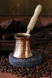 Copper coffee pot with beans. On a wooden table Royalty Free Stock Photo