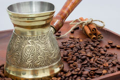 Copper coffee pot with coffee beans and cinnamon sticks. On a wooden plate board. White background Royalty Free Stock Photos