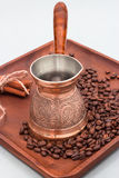 Copper coffee pot with coffee beans and cinnamon sticks. On a wooden plate board. stock image