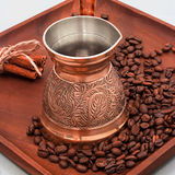 Copper coffee pot with coffee beans and cinnamon sticks. On a wooden plate board. White background. Square image. royalty free stock photo