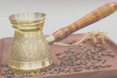 Copper coffee pot or ibrik with coffee beans and cinnamon sticks. On a wooden plate board. White background Stock Photography