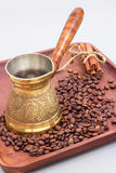 Copper coffee pot or ibrik with coffee beans and cinnamon sticks. On a wooden plate board. White background royalty free stock image