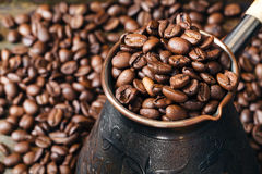 Copper coffee pot for preparation of coffee on  scattered coffee. Grains Royalty Free Stock Image