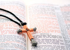 Copper colored cross on open Bible Stock Images