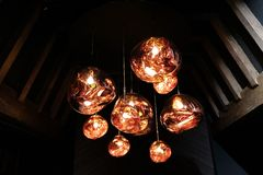 Copper colored glass pendant light fitting hanging in attic with wooden beams stock images