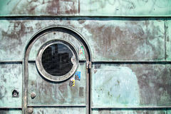A copper door found in Copenhagen denmark. Copper door with porthole and glass. Worn green in Copenhagen Denmark stock photography