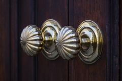 Copper door handles shot close-up. Against the door royalty free stock photography