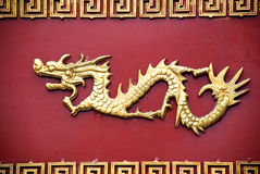Copper dragon on the door. A flying copper dragon sculpture on the red wood door, the totem of the Chinese People Stock Photo