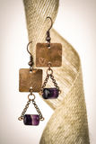 Copper earrings with purple stones Royalty Free Stock Image