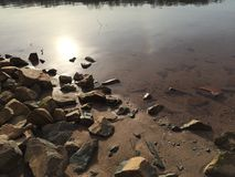 Copper Glimmer. Lakeside shore of rocks stock photography