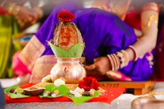 Copper kalash with coconut and mango leaf with floral decoration royalty free stock photography