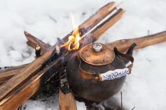 Copper kettle over an open fire in winter Stock Photo