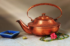 Copper Kettle Still Life. A copper kettle and tea pearls on a tile table with a sunbeam in the background Stock Photos